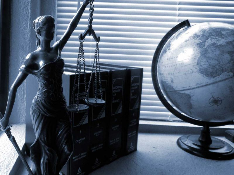 Justice Statue with Legal books and globe
