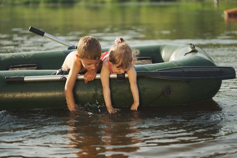 boy and girl on a raft in a lake