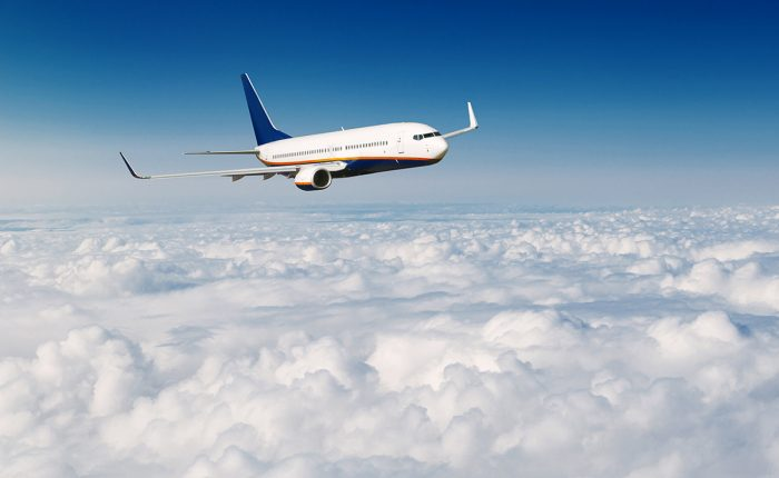 Commercial Airplane Flying Above Clouds On Blue Sky Background.
