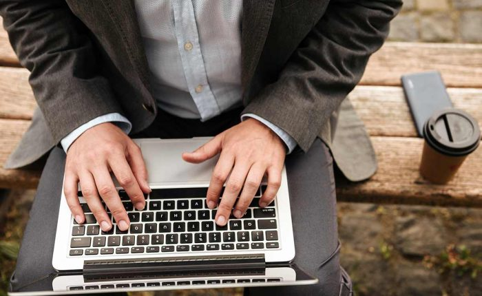 Man sitting on a park bench using a computer