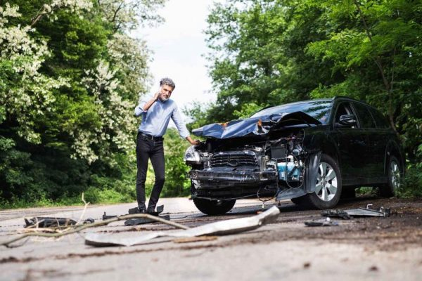 Mature Man Standing By Wrecked Car Making A Call
