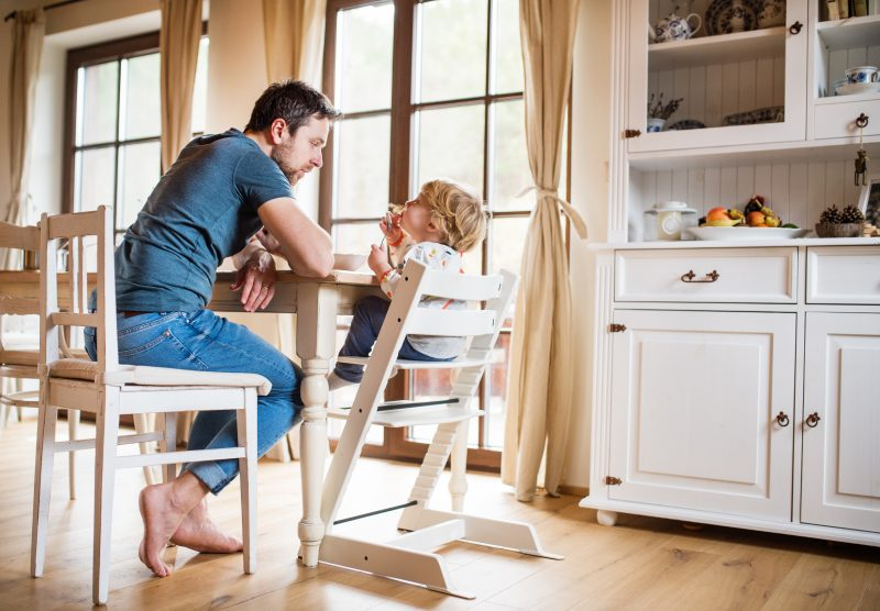 Father Sitting At The Table With A Toddler Boy At Home.
